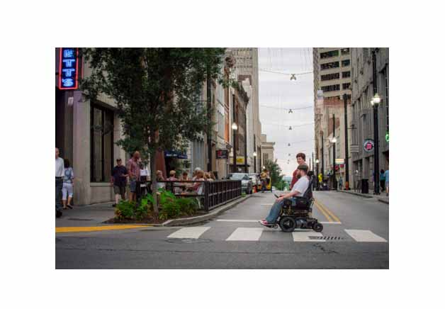 a wheelchair user and his friend going across the road on a cross walk