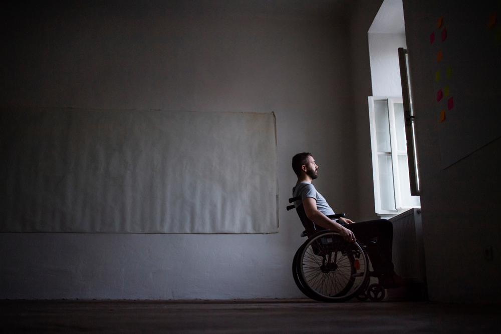 Man in wheelchair looking out of the window.