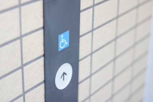 elevator up button next to a handicap icon