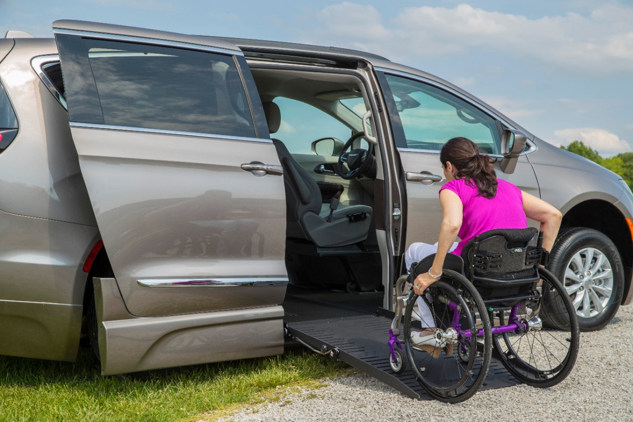 Woman in manual wheelchair acends the ramp in a BraunAbility Chrysler Pacifica Foldout