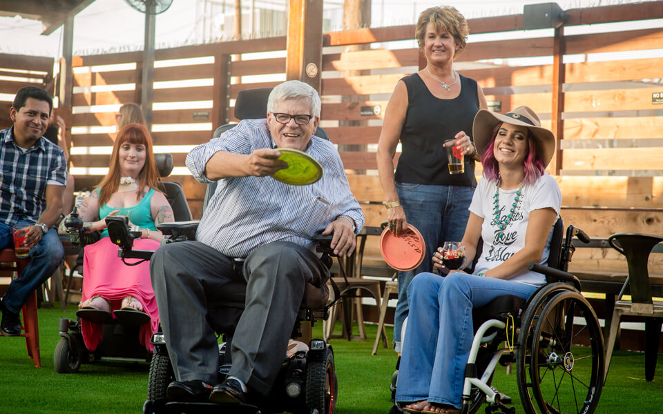 A group of wheelchair users play disc golf outside of a brewery