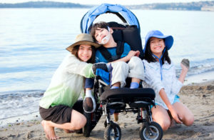 Mom and two young kids, one in a wheelchair, enjoys a day at the beach