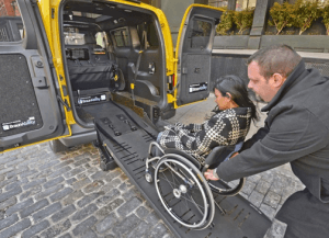 Woman in wheelchair being loaded into an NV200 wheelchair accessible taxi