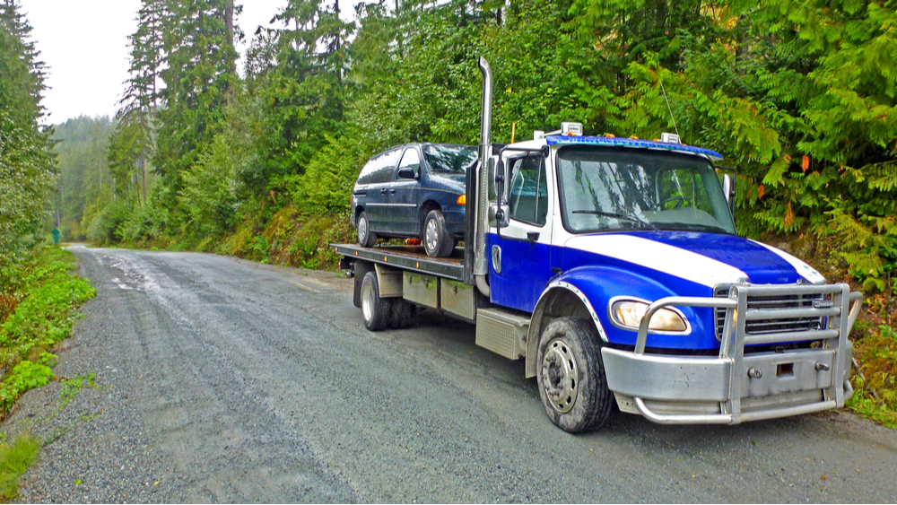 A flatbed tow truck towing a minivan