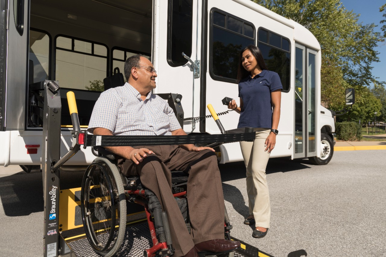 man exiting a bus in his wheelchair on a wheelchair lift with the help of a care taker