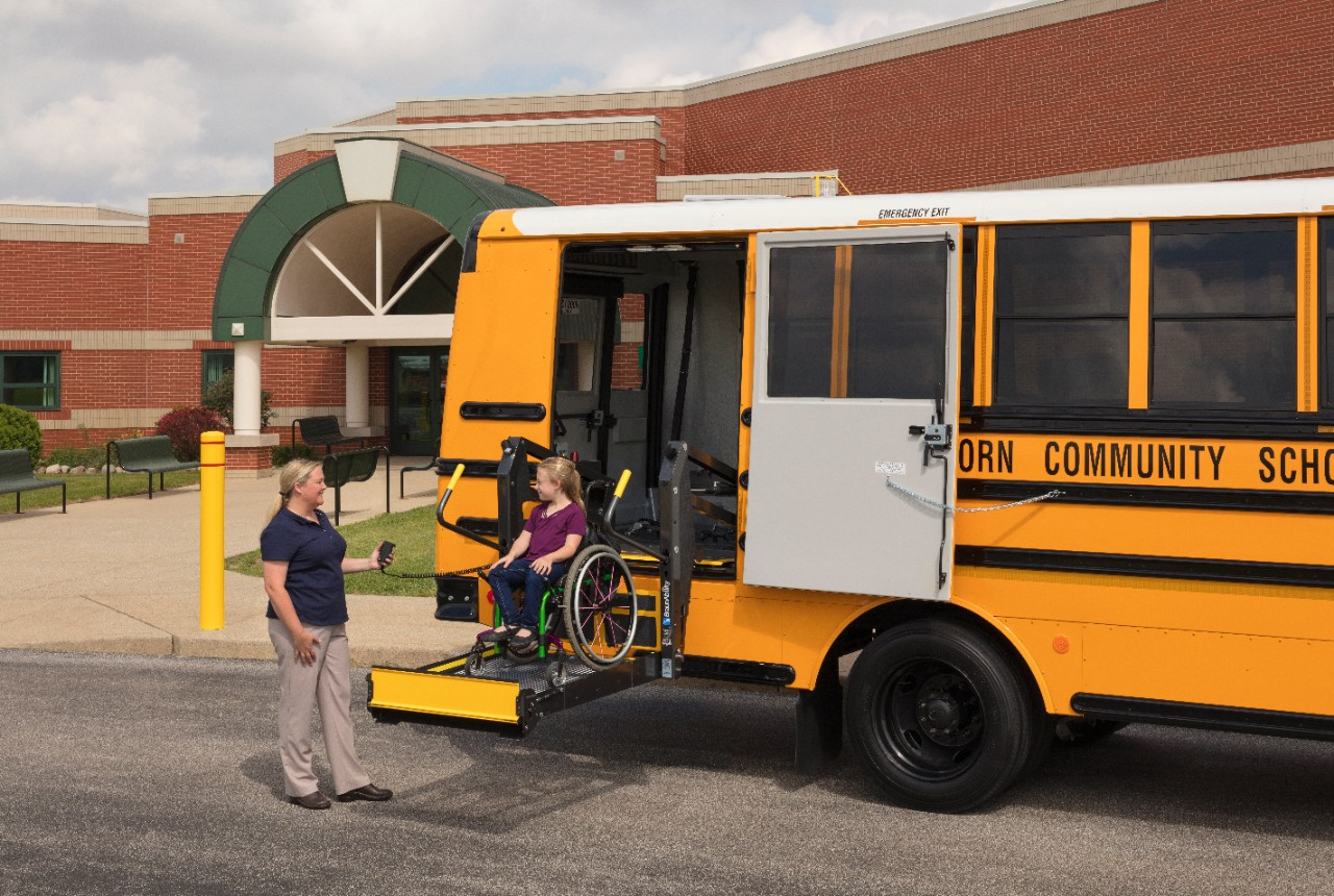 little girl and caregiver using a BraunAbility wheelchair lift on a school bus