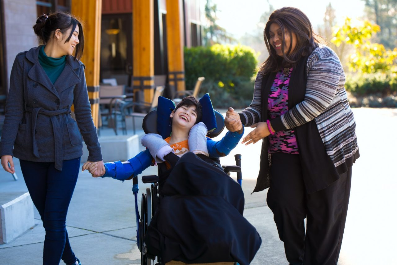a young person in a wheelchair surrounded by loving people