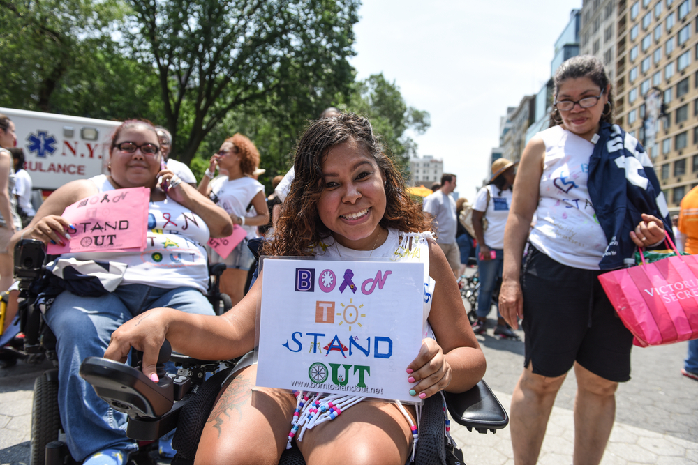 a girl holding a born to stand out sign at a rally in new york city