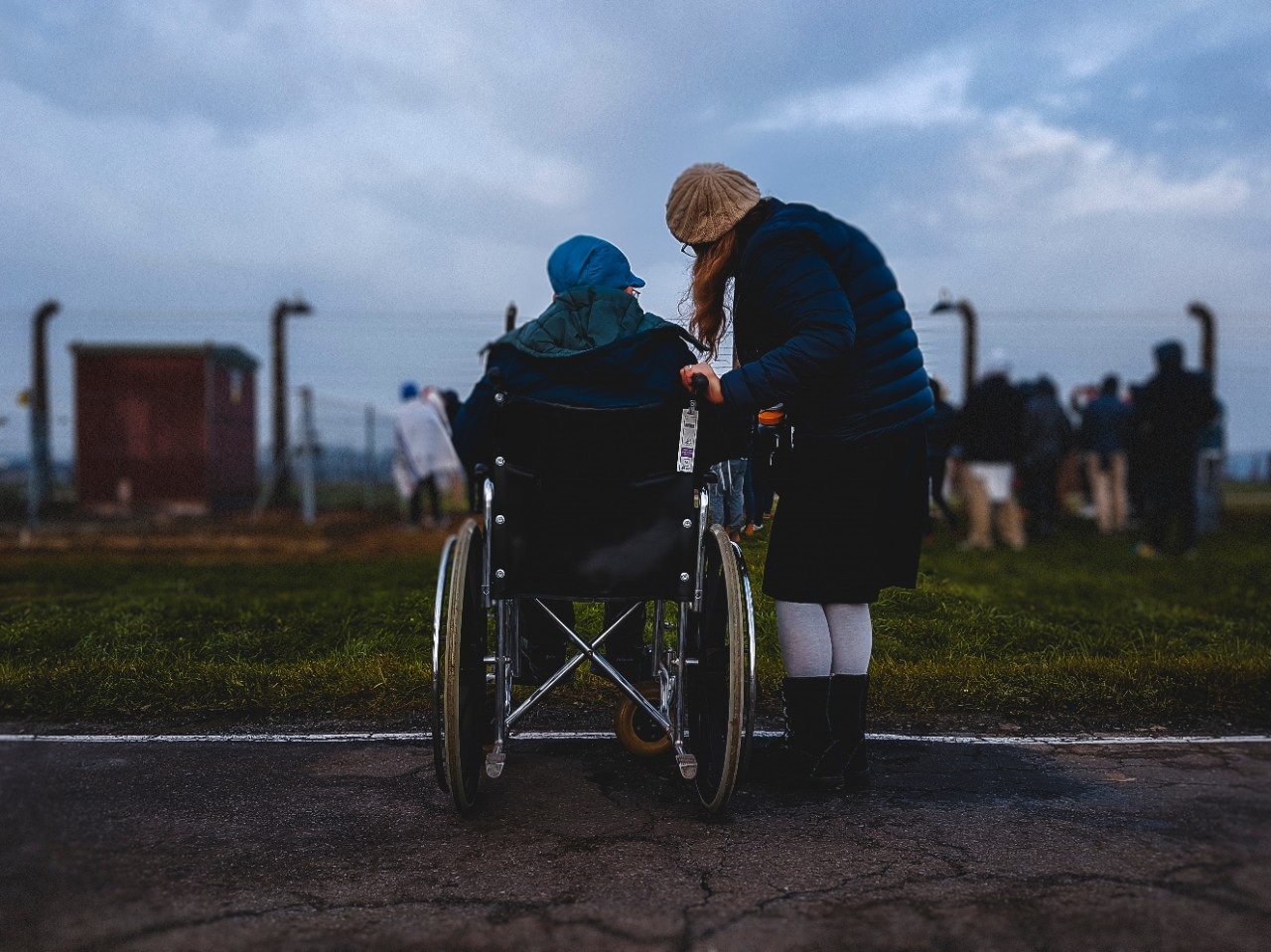 A wheelchair user and friend looking over at a group of people