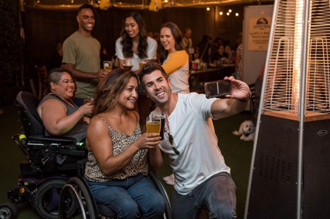 wheelchair users at a inclusive party taking a selfie while having fun