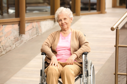 Happy senior woman in wheelchair near ramp outdoors
