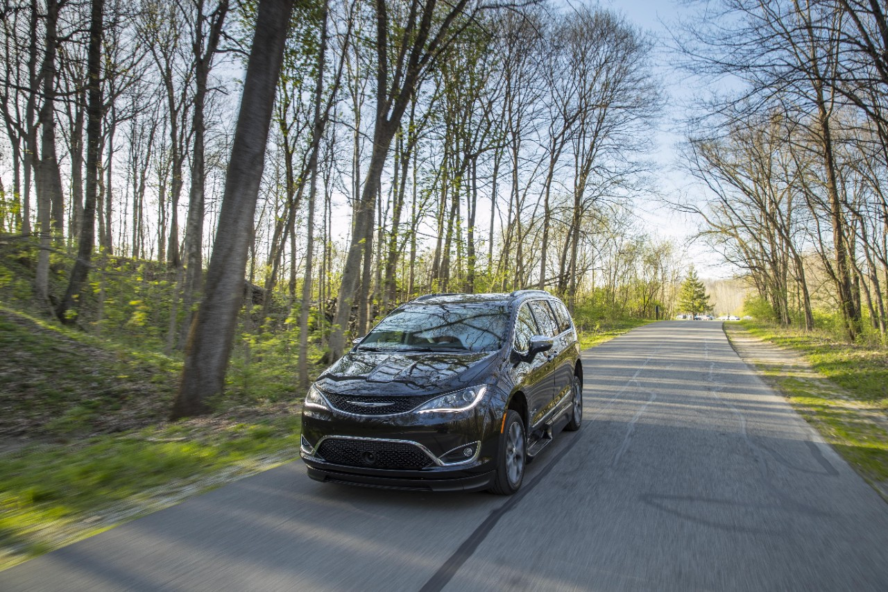 BraunAbility Chrysler Pacifica driving through a wooded road