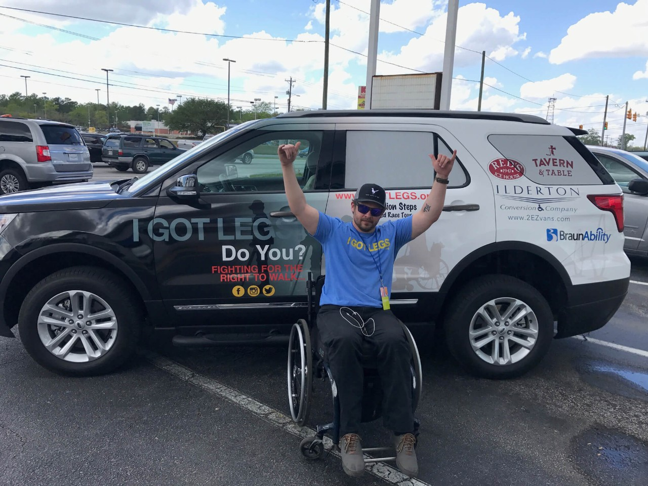 Adam Gorlitsky sits in a wheelchair in front of a BraunAbility MXV and raises his hands in triumph
