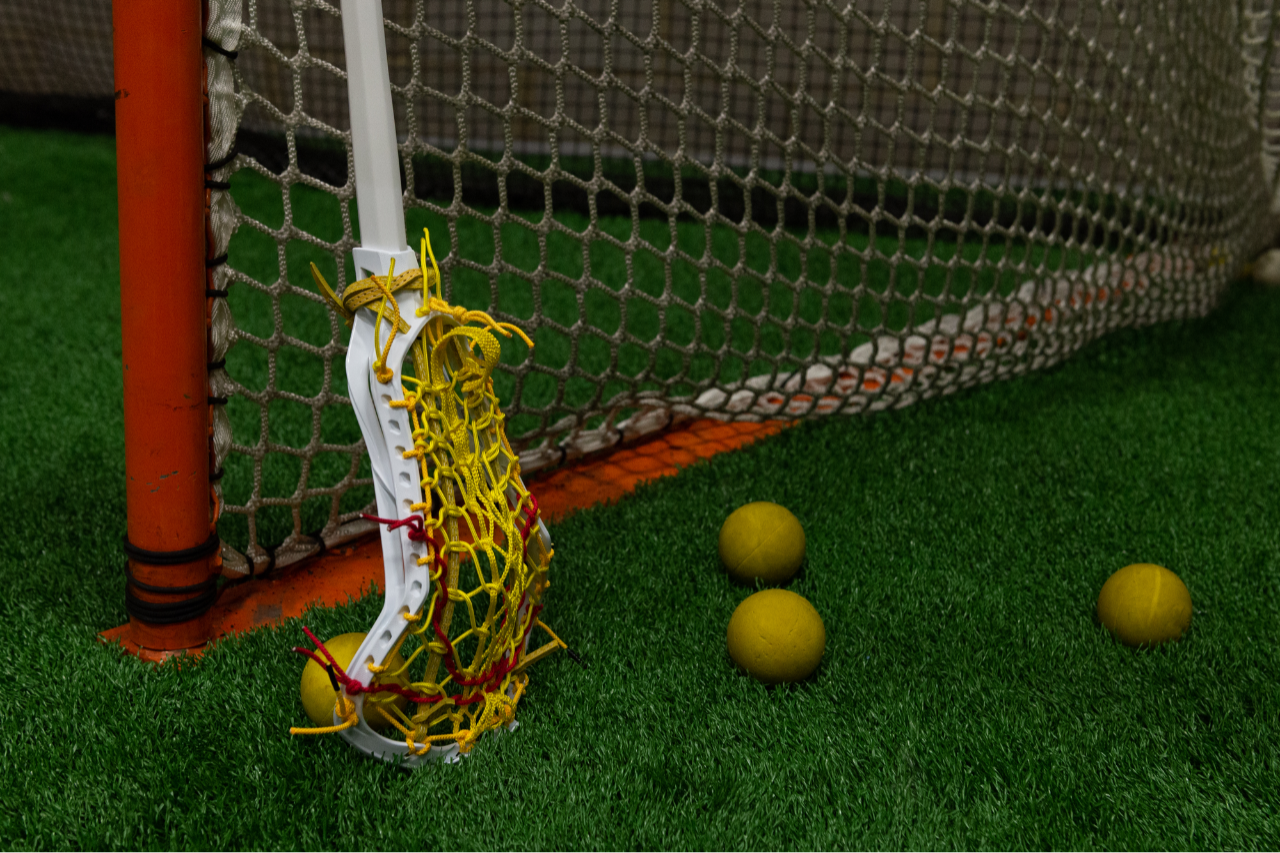 Woman's lacrosse stick leaning against a goal post with lacrosse balls nearby