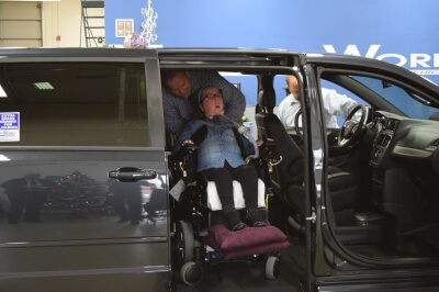 Lauren Gross exits a side-entry BraunAbility vehicle in a MobilityWorks dealership