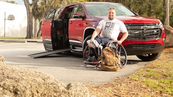 a veteran sitting next to his wheelchair suv chevy traverse